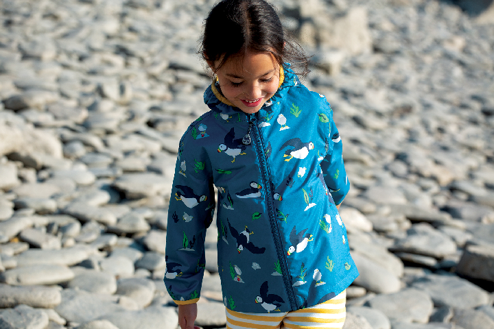 Yound Dark Girl with dark hair with a blue Pioneer Packaway Jacket, with picturs of puffins on it, as she walks on a pebble beach.