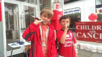 Singing for charity in Southport are volunteers Oliver Bailey (10) from Leyland Road, Southport and (right) Dylan Bennett (8) from Maxton Road, Liverpool.