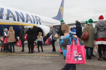 Children from Alder Hey with parents and Airport employees excitedly boarding the special Ryanair flight at LJLA.