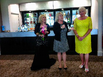 Julie A. Scott (singer) presented with flowers by the Lady Captain of Hillside Golf Club and Olive Cutts