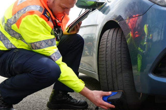 Highways England Traffic Officer Neil Waring, from Knutsford outstation, checking car tyres at 1 of Cheshire's charity car wash events in March 2018.