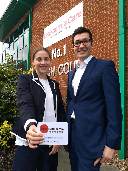 Bethany Torr and Zack Pemberton-Whiteley from Leukaemia Care with the leukaemia symptoms card.