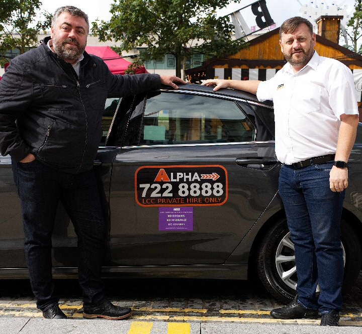 Liverpool City Council's Cabinet Member for Transport Cllr James Noakes shows off the new signs with Alpha Operations Manager Liam Sweeney.
