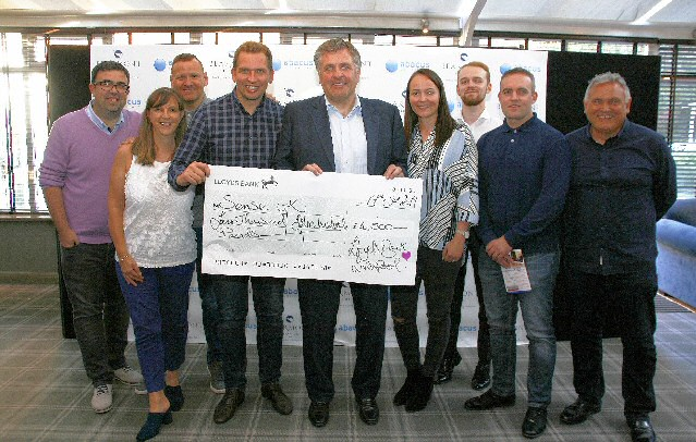 Liverpool City Center Lloyds Bank staff in group handing over the check Cheque. In the photo with Jan Molby are:- Phil Burton, James Fielding, Paul Convey, Damien Tilyer, Phil Nebb, Lucy Osborne, Joanne Mellitt,