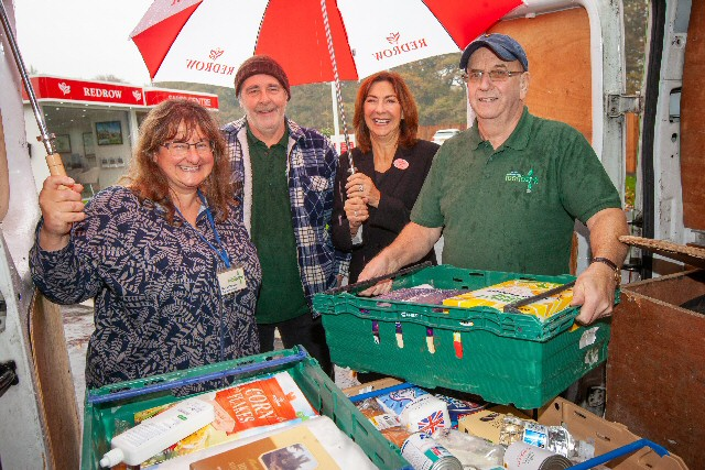 South Liverpool Foodbank's Nicola Hawkes, Billy Breden and Phil Keating collect a food parcel from Redrow's Helen Pirie